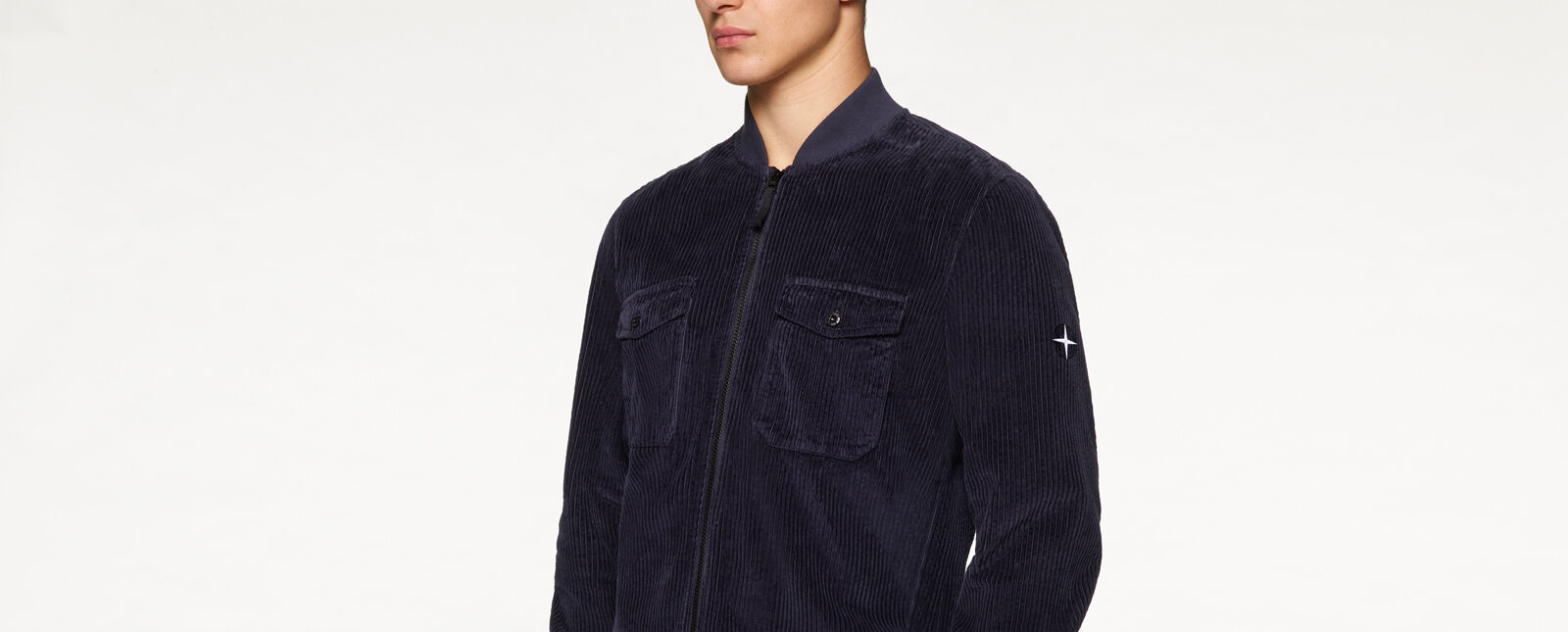 Close up shot of model wearing a dark blue corduroy bomber jacket with zipper fastening, two chest pockets with flap and button and the two-tone blue and white Stone Island Compass Rose embroidery on the upper left sleeve.
