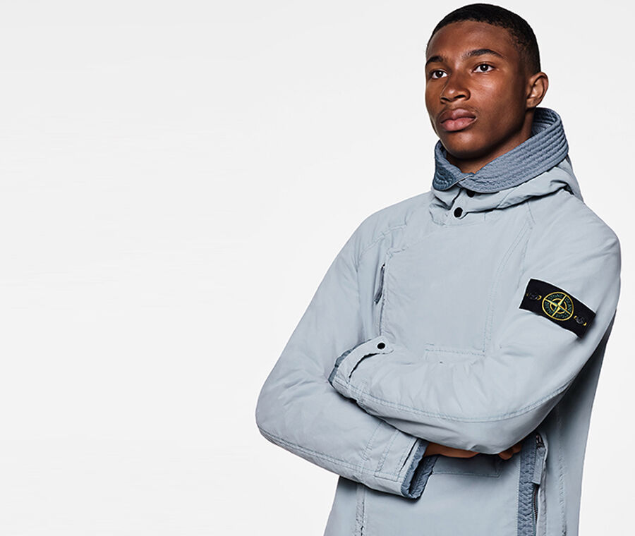 Close up shot of model wearing a light gray jacket with standing collar, diagonal two way zipper fastening, strap at cuffs held by a snap and the Stone Island badge on the upper left sleeve.