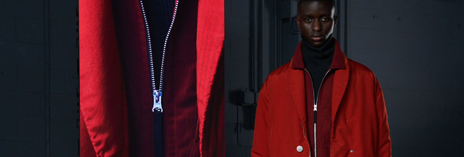 Model wearing a dark red jacket with high collar and a red overcoat beside an extreme close-up of the jacket zipper.