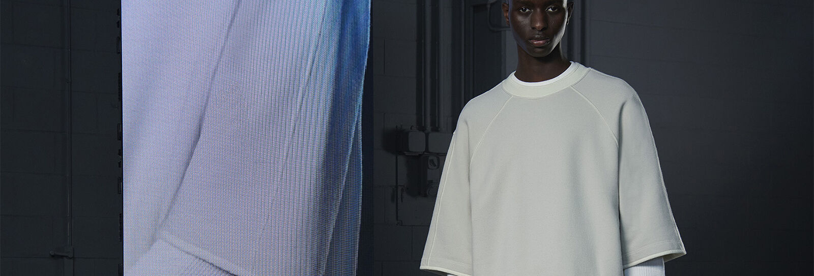 Model wearing a an oversized light gray t-shirt beside an extreme close-up of the sleeve.