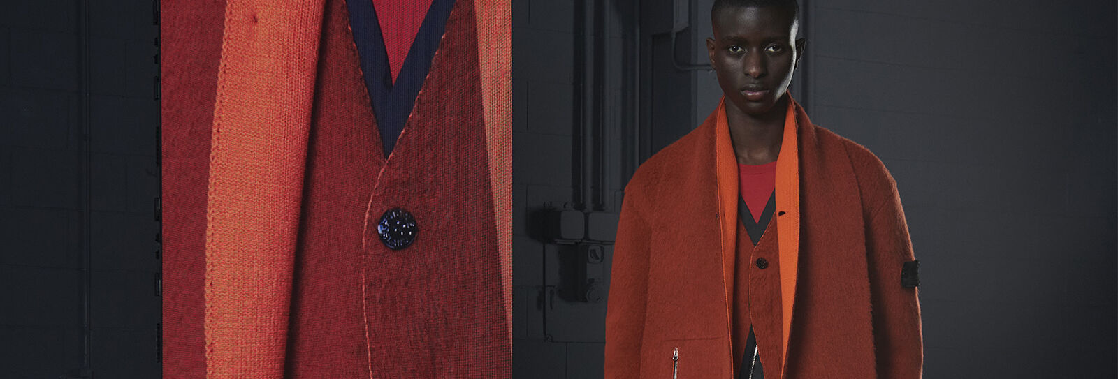 Model wearing a red and blue sweater under a two-tone orange, buttoned coat beside an extreme close-up of button.