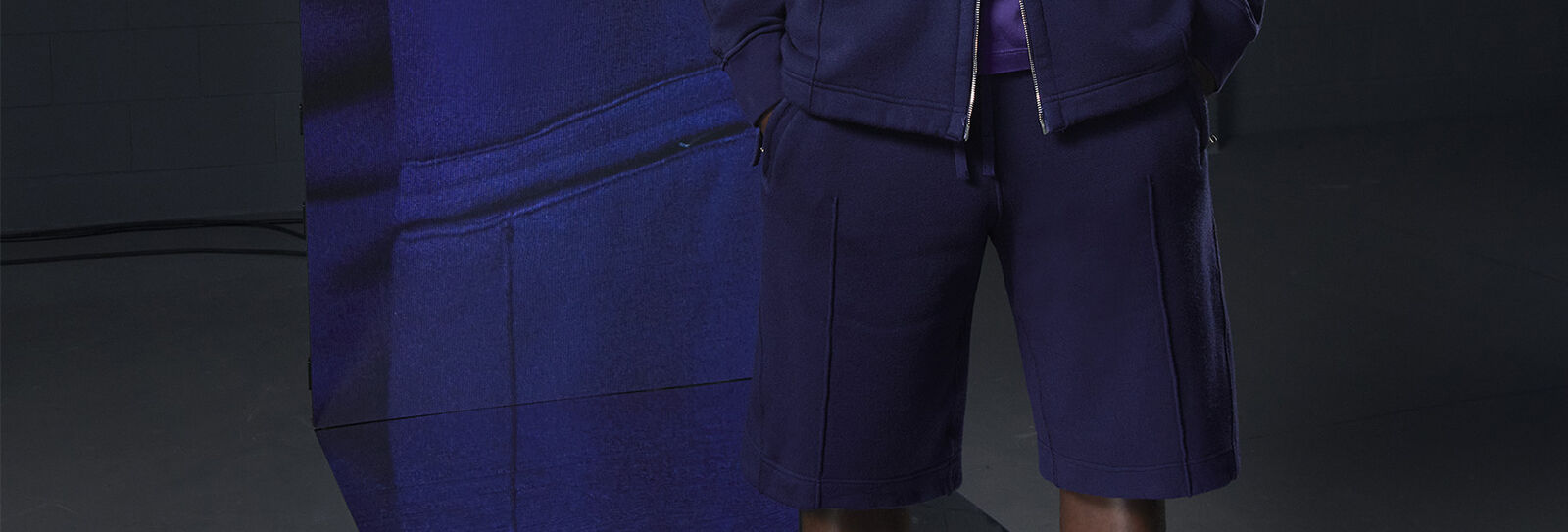 Close-up of model wearing blue t-shirt, jacket and shorts alongside an extreme close-up of the stitching.