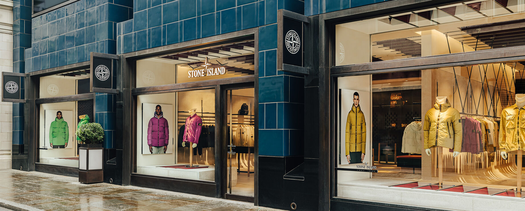 Angled view of storefront with three window displays of various jackets.