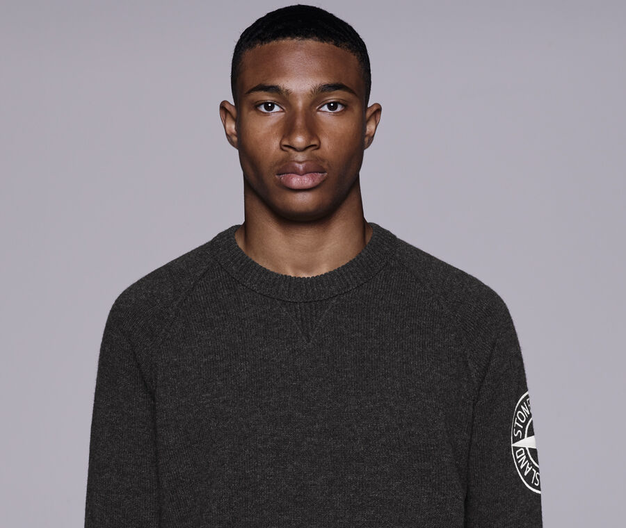Model wearing a dark colored mélange crewneck sweater with raglan sleeves, white embroidery of the Stone Island Compass logo on the left sleeve and ribbed neckline, cuffs, and bottom band.