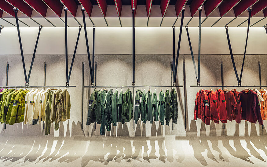 Three clothes racks, fixed to the wall and suspended from the ceiling, display jackets, sweaters and t-shirts.
