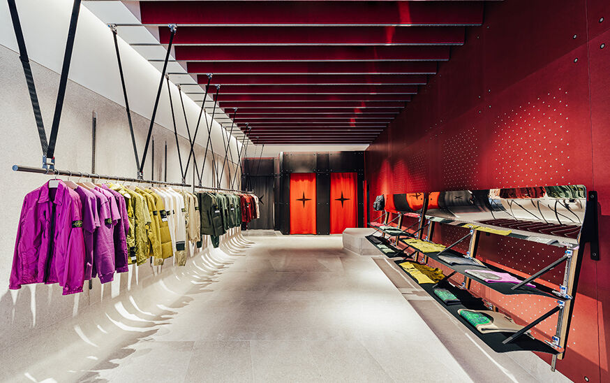 Contemporary clothes racks and shelves display clothes in front of three doorways, two with red curtains and one with black.