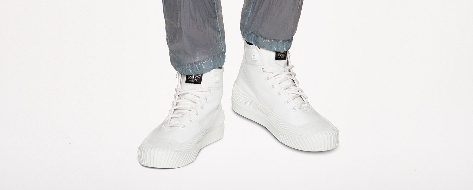 Close-up of model wearing white high-top laced sneakers with the Stone Island badge on the tongue.