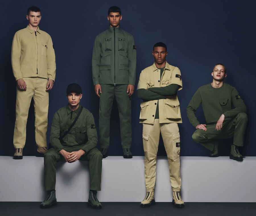 Five models set against a navy blue backdrop. Three wearing various dark green jackets, sweaters, pants and boots; one wearing a khaki jacket, pants and boots and the other wearing a dark green sweatshirt combined with a short-sleeved khaki jacket, pants