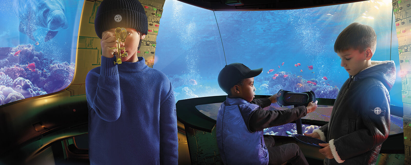 In the water, three junior models inside a deep sea shuttle, one wearing a blue sweater and black ribbed beanie, the second one a blue vest and a black cap and the third one a sheepskin jacket with hood and white lining.