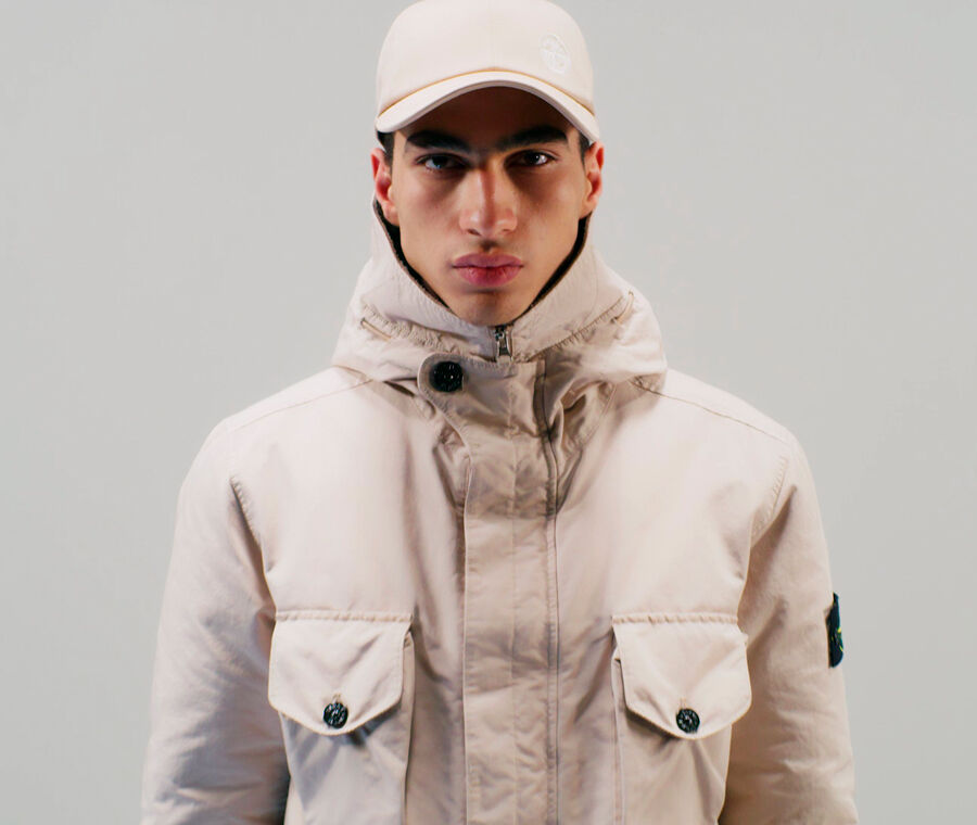 Close up shot of model wearing an off white cap and a matching jacket with hood, central fastening hidden by a flap and two chest pockets with flap and button fastening.