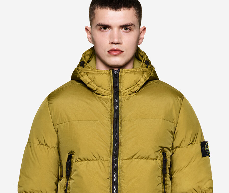 Model wearing dark colored pants and a mustard down jacket with hood, black zipper fastening, two side pockets with zipper and the Stone Island badge on the upper left sleeve.