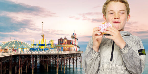 Junior model eating a doughnut in front of the Brighton Pier amusement park, wearing a dust-effect gray, half-zip jacket with the Stone Island badge on the upper left sleeve.