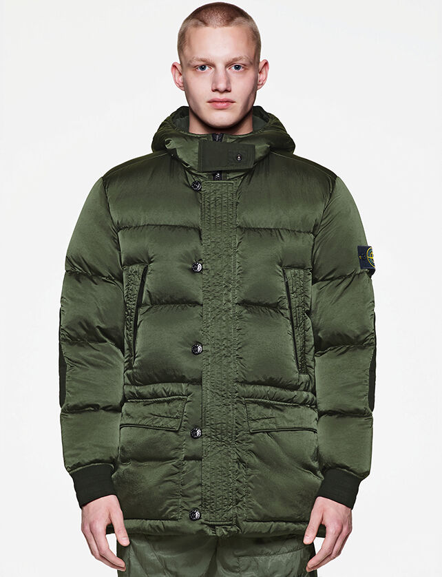 Model wearing a dark green jacket with a zipper hidden by a buttoned flap, two front zipped pockets, two front flap pockets and the Stone Island badge on the upper left sleeve.