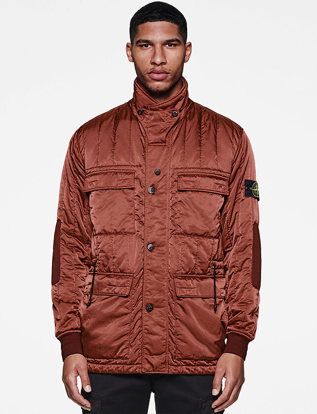 Model wearing a light maroon buttoned jacket with a high buttoned collar, two chest flap pockets, two large flap pockets and the Stone Island badge on the upper left sleeve.