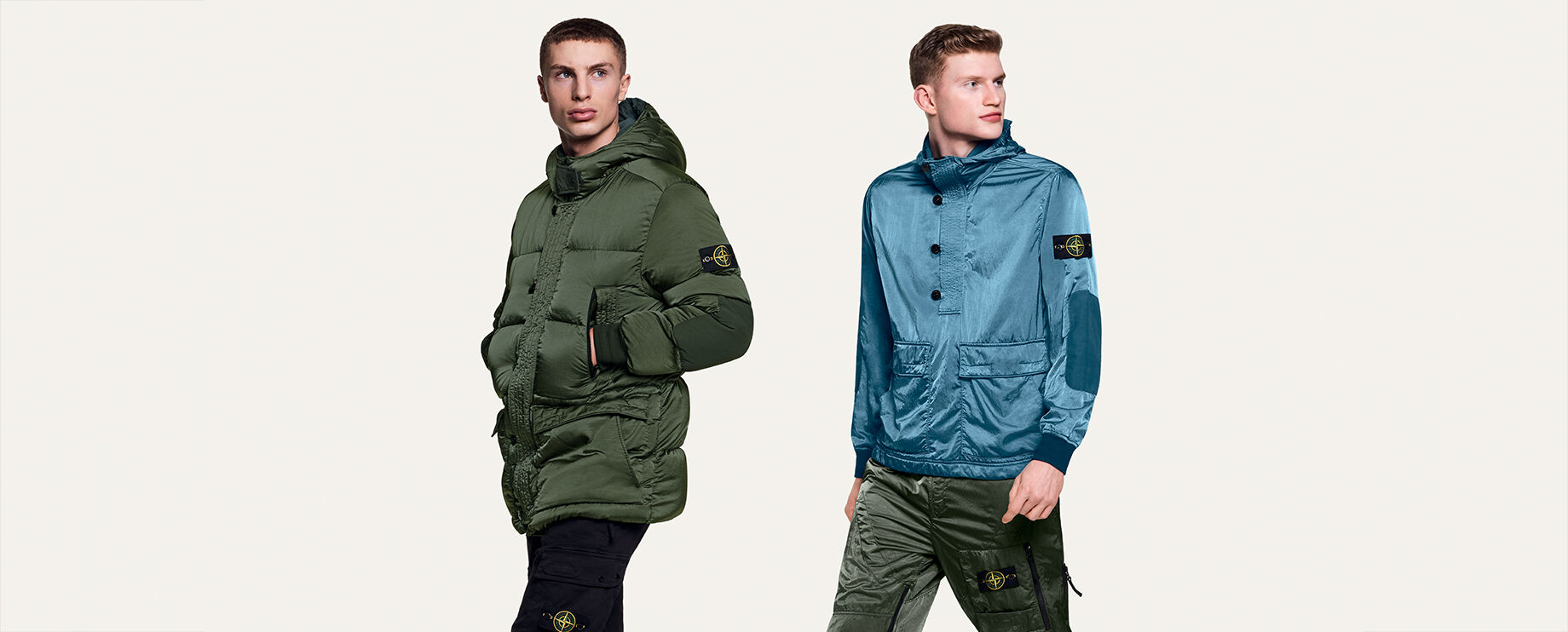 Model in mid-stride wearing a light blue, half-buttoned jacket with two front flap pockets and the Stone Island badge on the upper left sleeve, as well as dark green pants featuring the badge on the left leg.