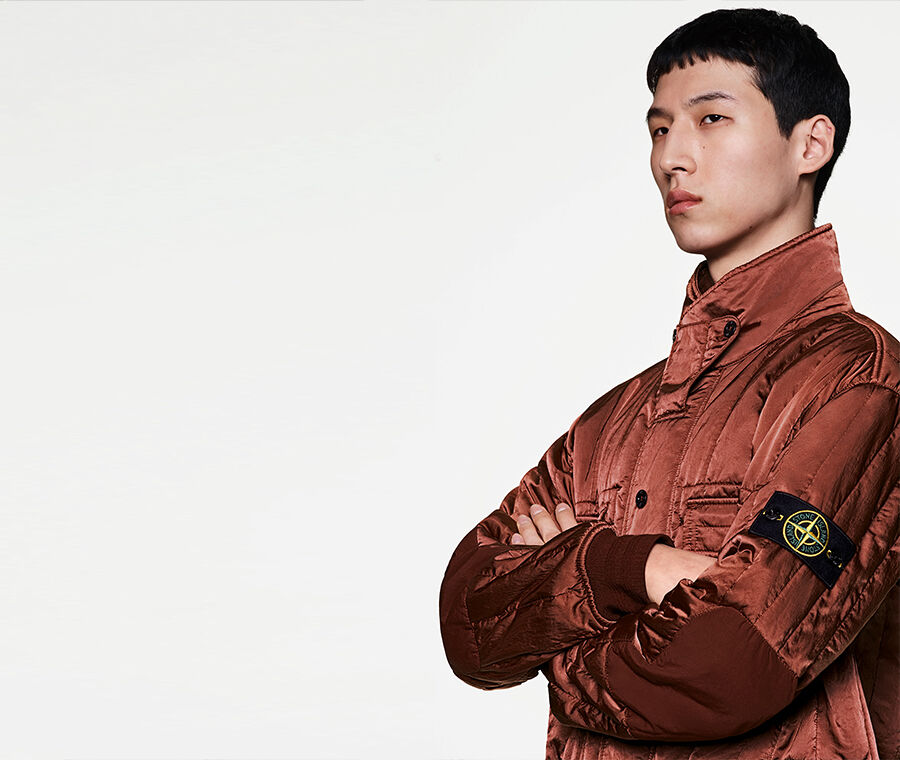 Model posed with crossed arms, wearing a light maroon jacket with a high, buttoned collar, dark elbow patches and cuffs, and the Stone Island badge on the upper left sleeve.