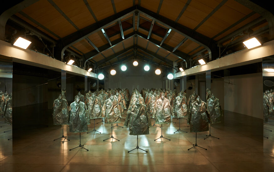 Numerous rows of Stone Island Prototype Research Series 05 Copper Nanotechnology jackets displayed in a warehouse setting under bright blue and yellow lighting.