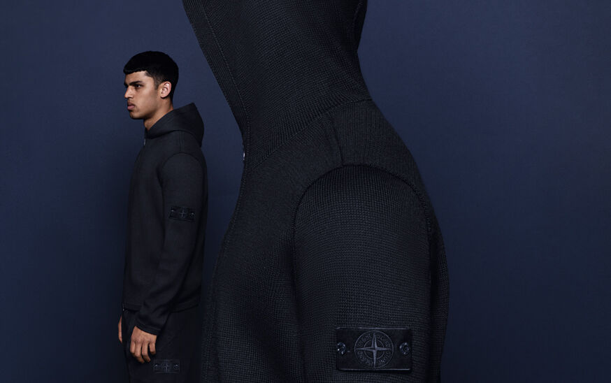 Model posed against navy background with a headshot in the foreground, wearing a black hooded sweater with Stone Island compass rose logo.