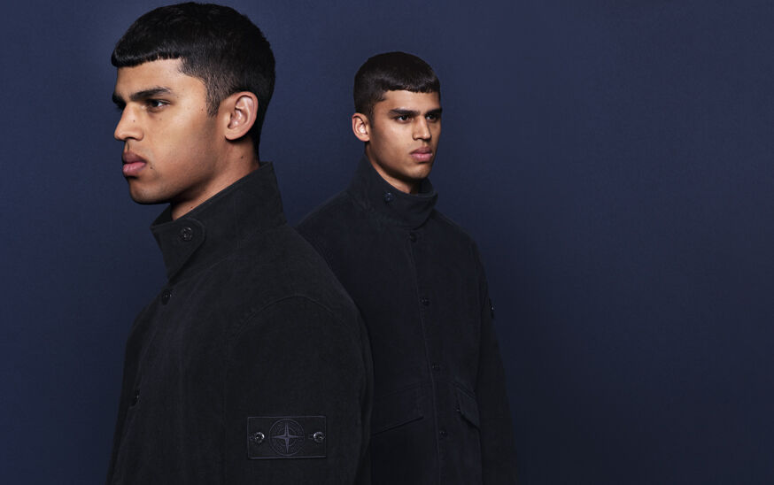 Model posed against navy background with a headshot in the foreground, wearing a black high collar buttoned jacket with Stone Island compass rose logo.