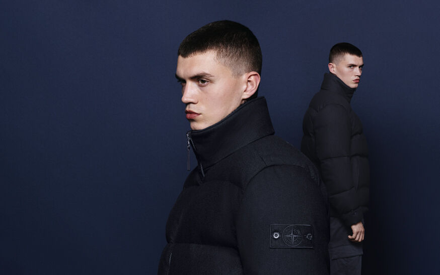 Model posed against navy background with a headshot in the foreground, wearing a padded high collar jacket with zipper and Stone Island compass rose logo.