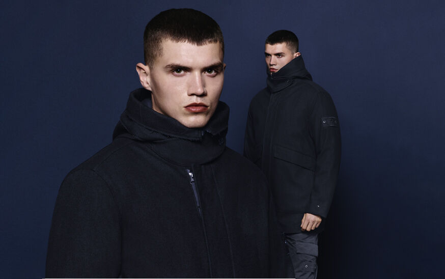 Model posed against navy background with a headshot in the foreground, wearing a black jacket with buttoned high collar, hood, concealed zipper and Stone Island compass rose logo.