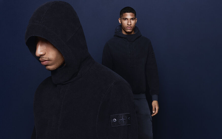 Model posed against navy background with a headshot in the foreground, wearing a hooded jacket with concealed zipper and Stone Island compass rose logo.