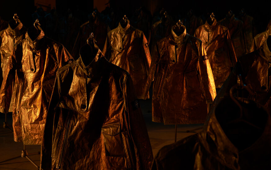 Numerous rows of Stone Island Prototype Research Series 05 Copper Nanotechnology jackets displayed under cold low-key lighting.