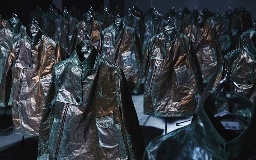 Numerous rows of Stone Island Prototype Research Series 05 Copper Nanotechnology jackets displayed under intense blue low-key lighting.
