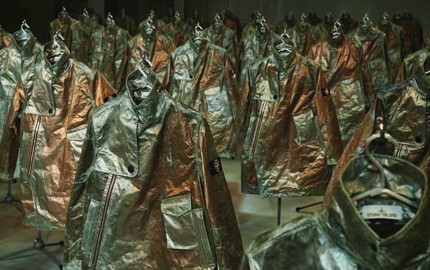 Numerous rows of Stone Island Prototype Research Series 05 Copper Nanotechnology jackets displayed under intense yellow lighting.