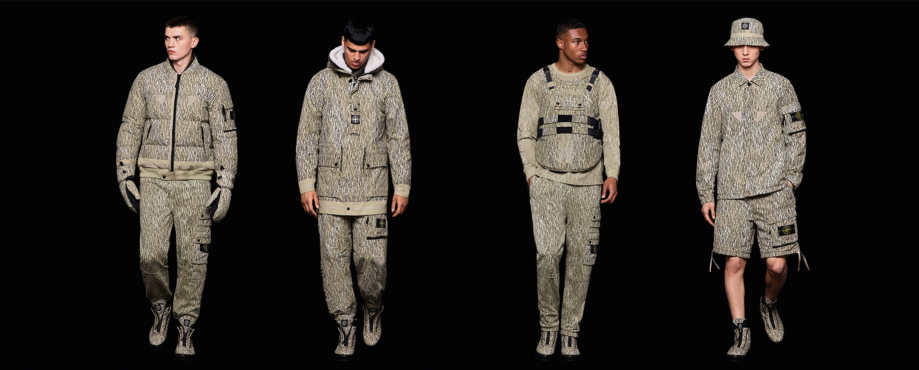 Four models in mid-stride wearing different khaki fall-winter outfits with garments featuring the same vertical line and subtle camo print.