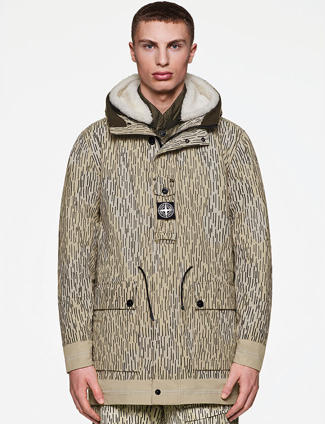 Model wearing a khaki camo print jacket with buttoned collar, lined hood, two pockets and central snap button pocket featuring the Stone Island badge.