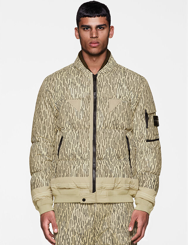 Model wearing a khaki camo print full-zip jacket with two zipped pockets and one flap pocket on the upper left sleeve featuring the Stone Island badge.