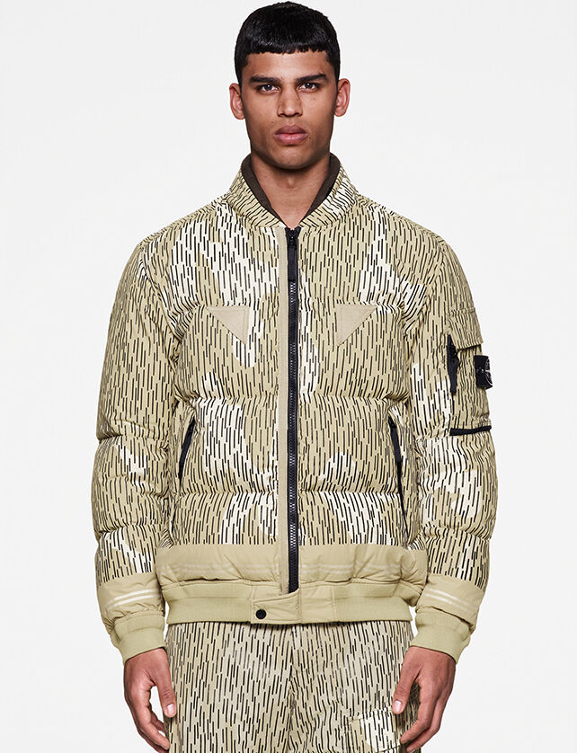 Model wearing a khaki reflective camo print full-zip jacket with two zipped pockets and one flap pocket on the upper left sleeve featuring the Stone Island badge.