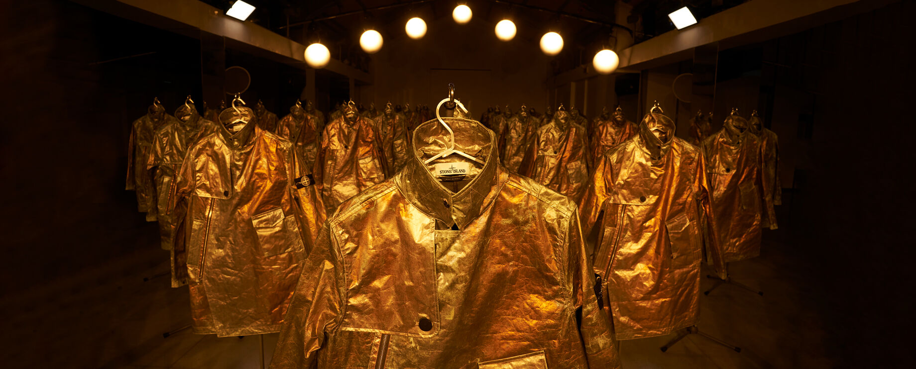 Numerous rows of Stone Island Prototype Research Series 05 Copper Nanotechnology jackets displayed in a warehouse setting under bright lighting.