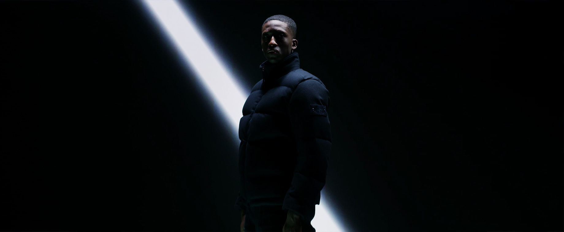 Model wearing a dark jacket in extreme low light, against a black backdrop with one diagonal beam of white light behind him.