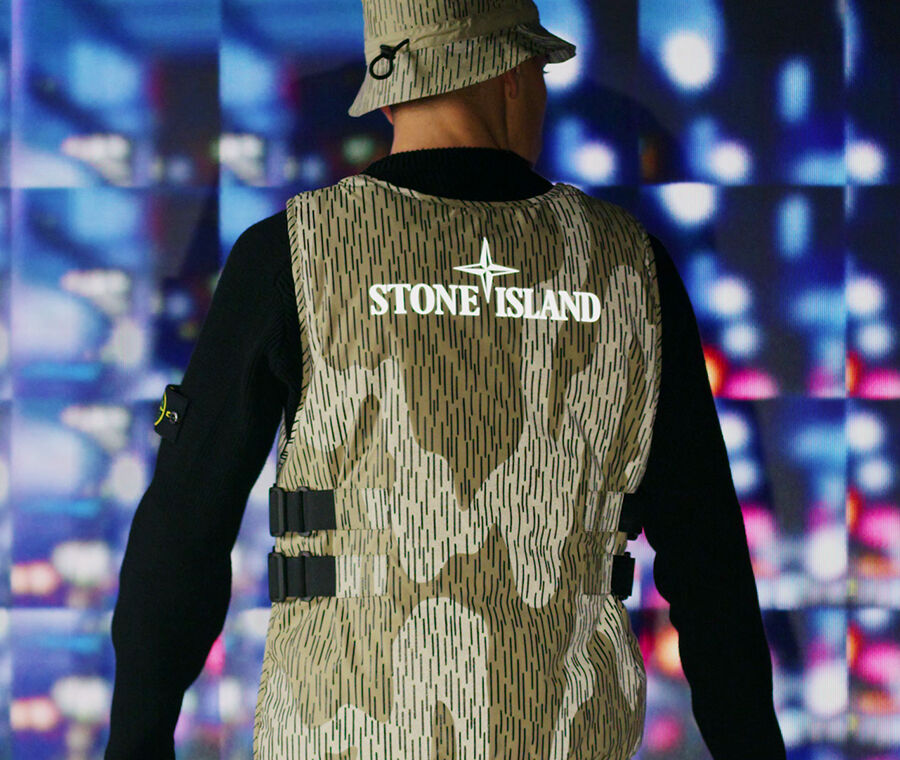 Model, shot from behind, wearing a black sweater; khaki vertical line and reflective camo print bucket hat and vest featuring a Stone Island graphic logo.