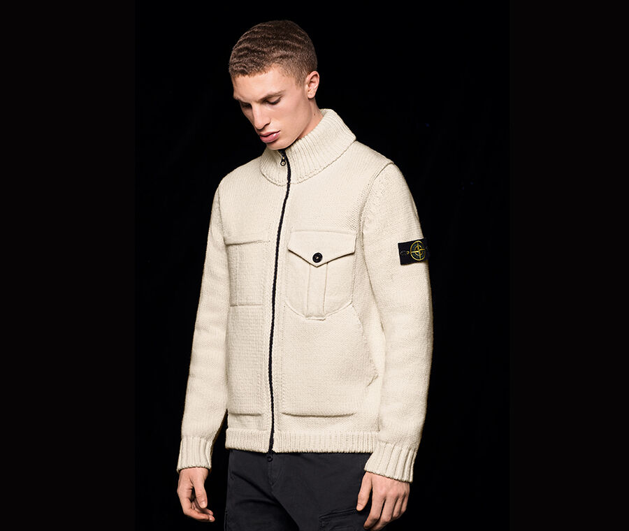 Model wearing a knit sweater with black zipper, one chest pocket featuring flap and button fastening; ribbed cuffs, hem and collar and the Stone Island badge on the upper left sleeve.
