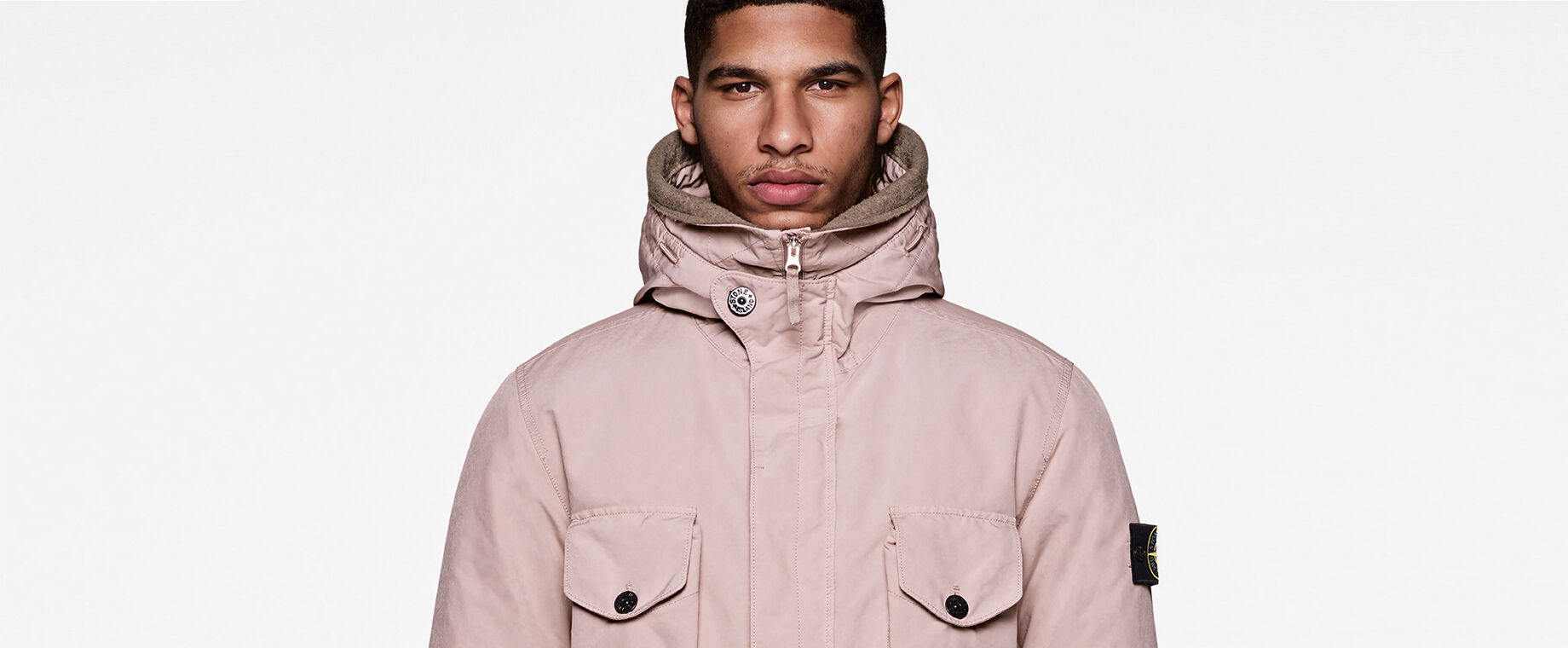 Model wearing a light pink hooded jacket with concealed full-zip fastening, four buttoned flap pockets and the Stone Island badge on the upper left sleeve.