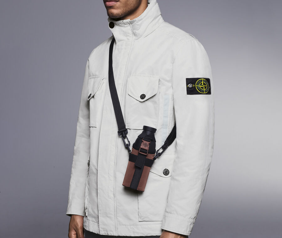 Model wearing an off-white jacket carrying a black canteen in a brown holster with a cross body strap.