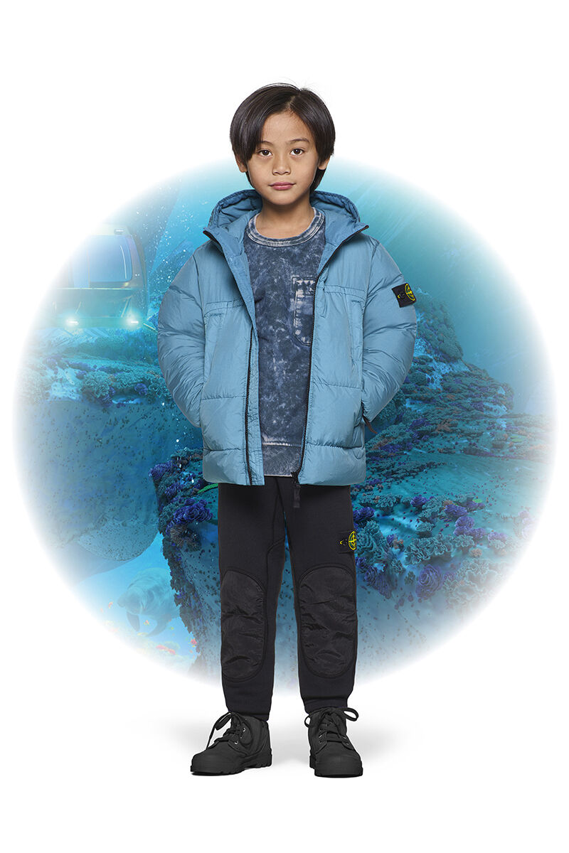Junior model with black boots, black cargo pants, a blue tie dye sweatshirt and a light blue down jacket with hood and side pockets.