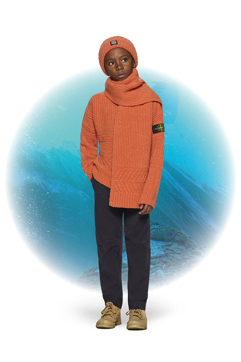 Junior model with khaki boots, black pants, an orange ribbed sweater with the Stone Island badge on the upper left sleeve, a matching scarf and beanie with turn up brim.