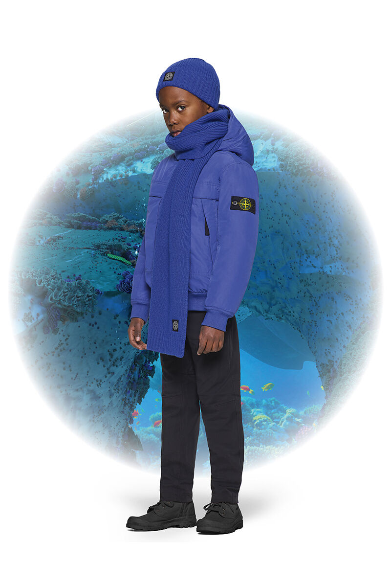 Junior model with black boots, black pants, a bright blue ribbed scarf, a matching beanie with turn up brim and a matching down jacket with hood and the Stone Island badge on the upper left sleeve.
