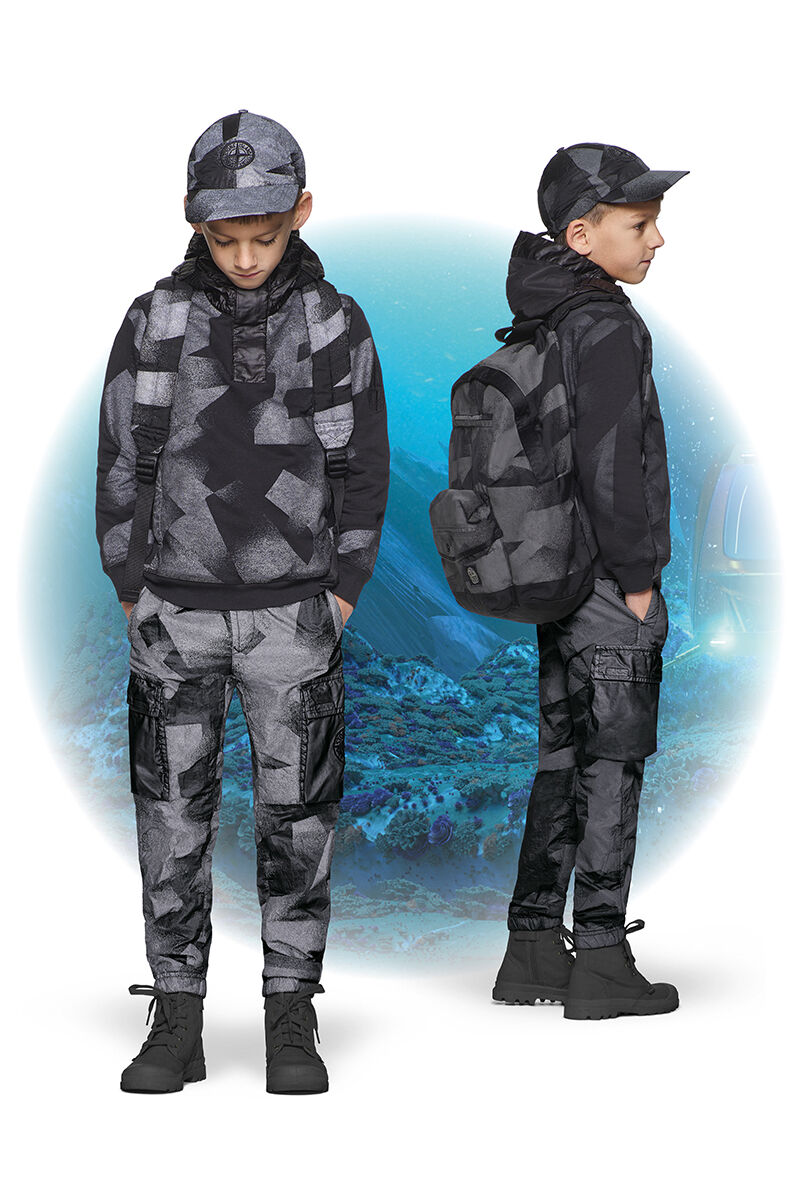 Two shots of the same junior model from the front and side, wearing black ankle boots, gray and black camouflage cargo pants, a matching hooded jacket, backpack and cap.