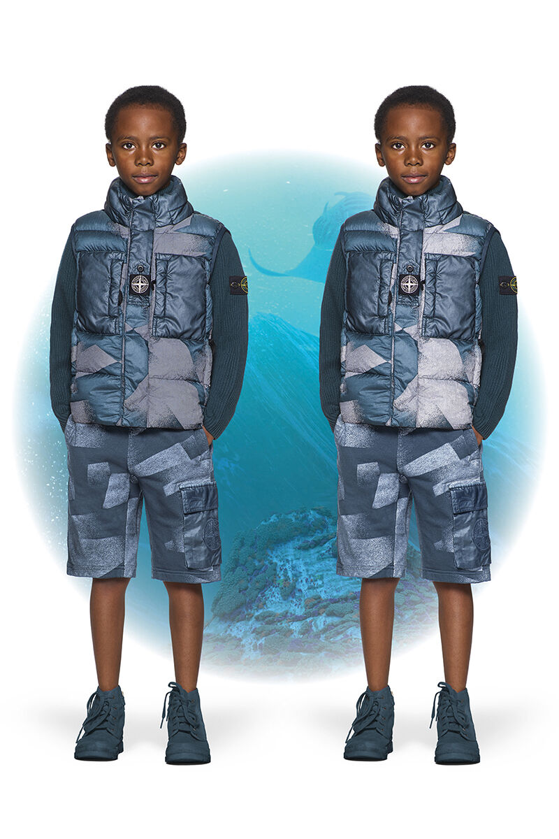 JTwo shots of the same junior model, wearing teal ankle boots, teal camouflage cargo shorts and a matching vest with standing collar and two chest pockets with flap.