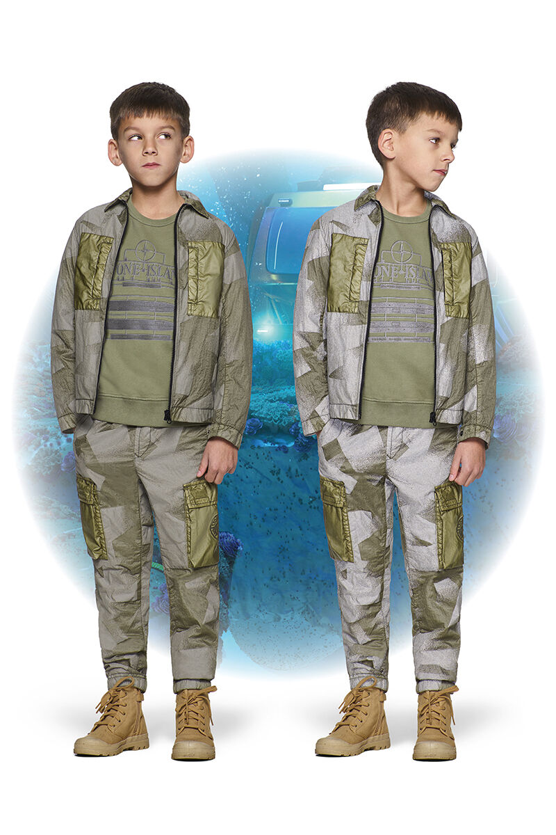 Two shots of the same junior model, wearing khaki ankle boots, a military green crewneck sweatshirt, green and gray camouflage cargo pants and a matching jacket with shirt collar and zipper fastening.