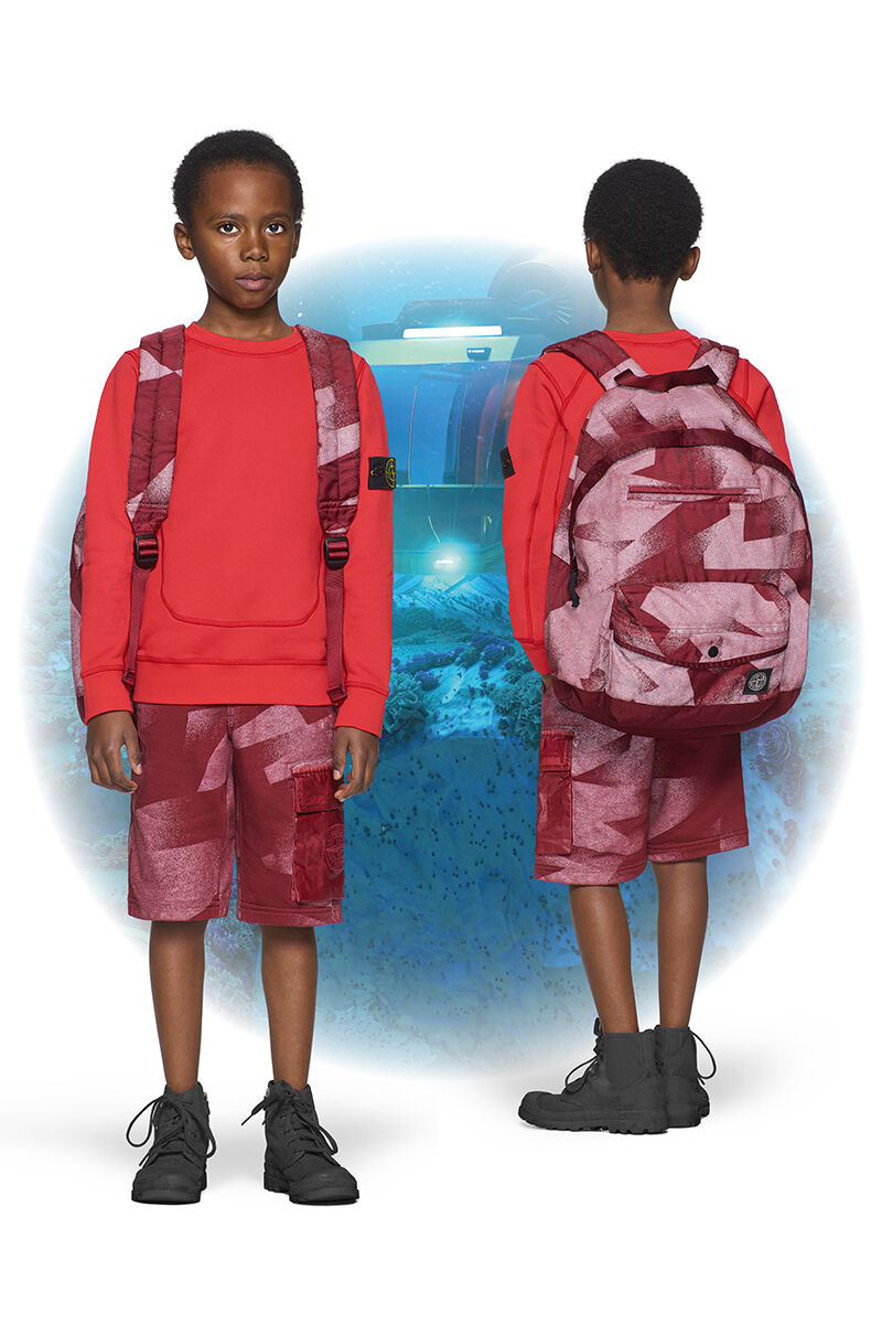 Two shots of the same junior model from the front and back, wearing black ankle boots, dark red camouflage cargo shorts, a matching backpack and a bright red crewneck sweatshirt.