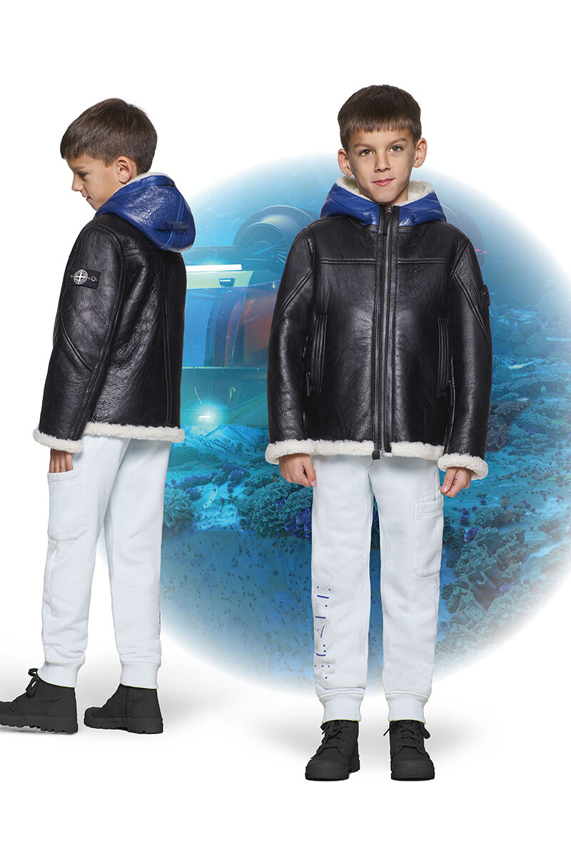 Two shots of the same junior model from the front and side, wearing black ankle boots, off white jogger sweatpants and a black sheepskin jacket with white lining and a blue hood.