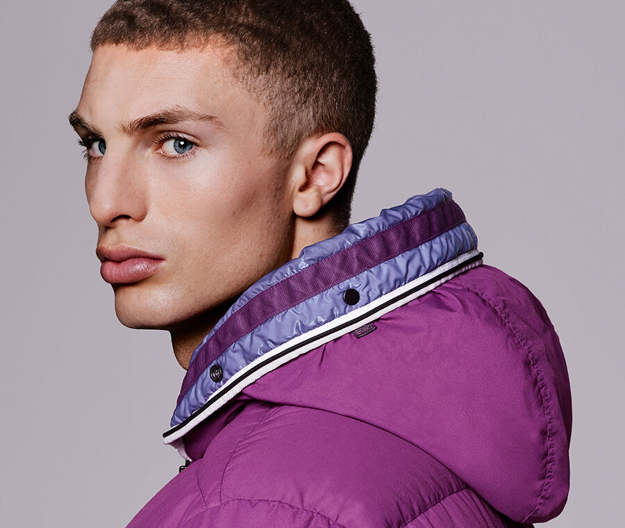 Close-up side view of model wearing a magenta hooded jacket with two-tone high collar and snap button detail.
